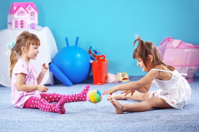 Bambine che giocano sul pavimento della camera da letto